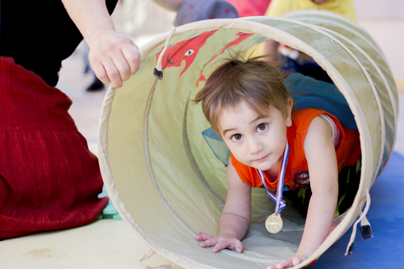 Child crawling through play tunnel. photo © Robin Spurs