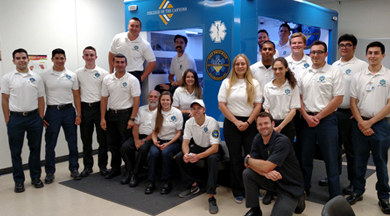 COC EMT students posing with Ambulance Simulator.