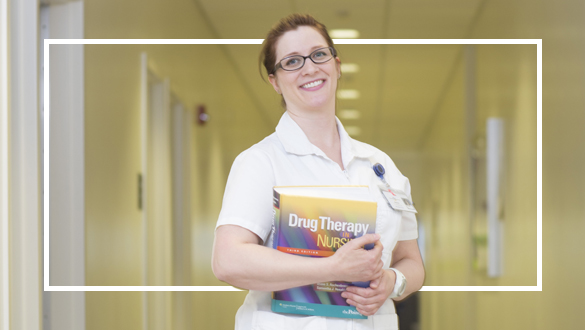 Nursing student posing with Drug Therapy book.