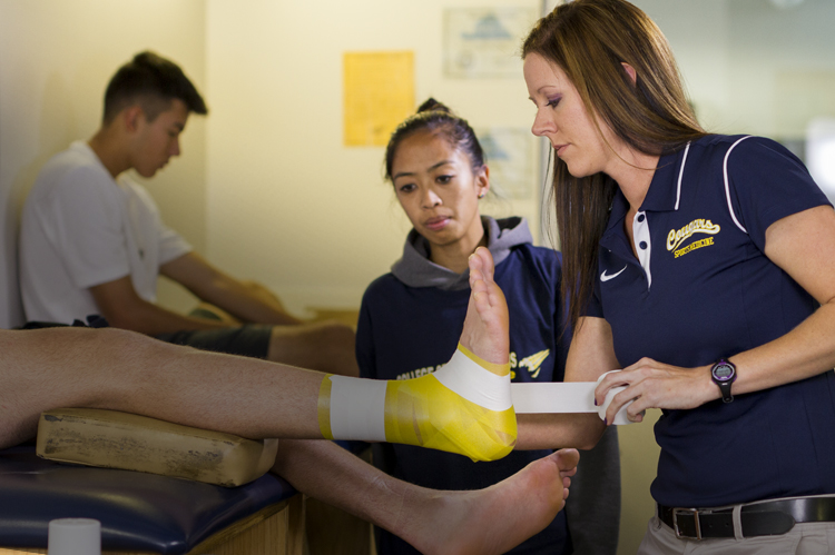 Sports Medicine faculty wrapping athlete's injuried ankle. photo © Robin Spurs