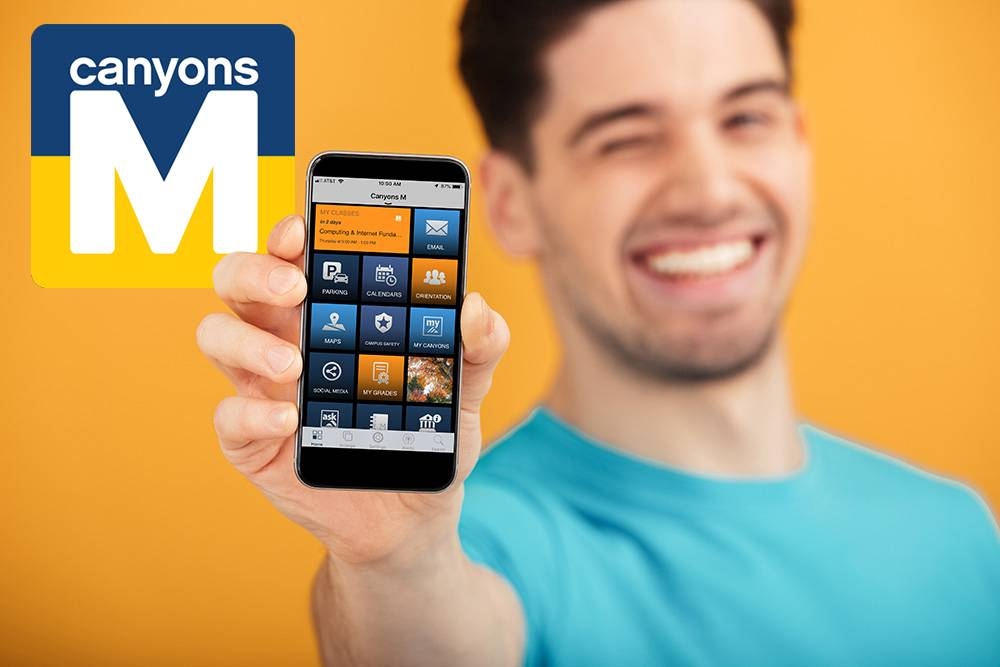 Male student holding smartphone displaying Canyons M app