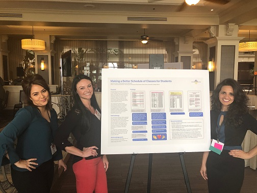 "Three presenters, from left to right, Vida Manzo, Catherine Parker, and Preeta Saxena, stand posing with their hands on their hips with a poster made by a Graphic Multimedia Design student titled ""Making a Better Schedule of Classes for Students"""