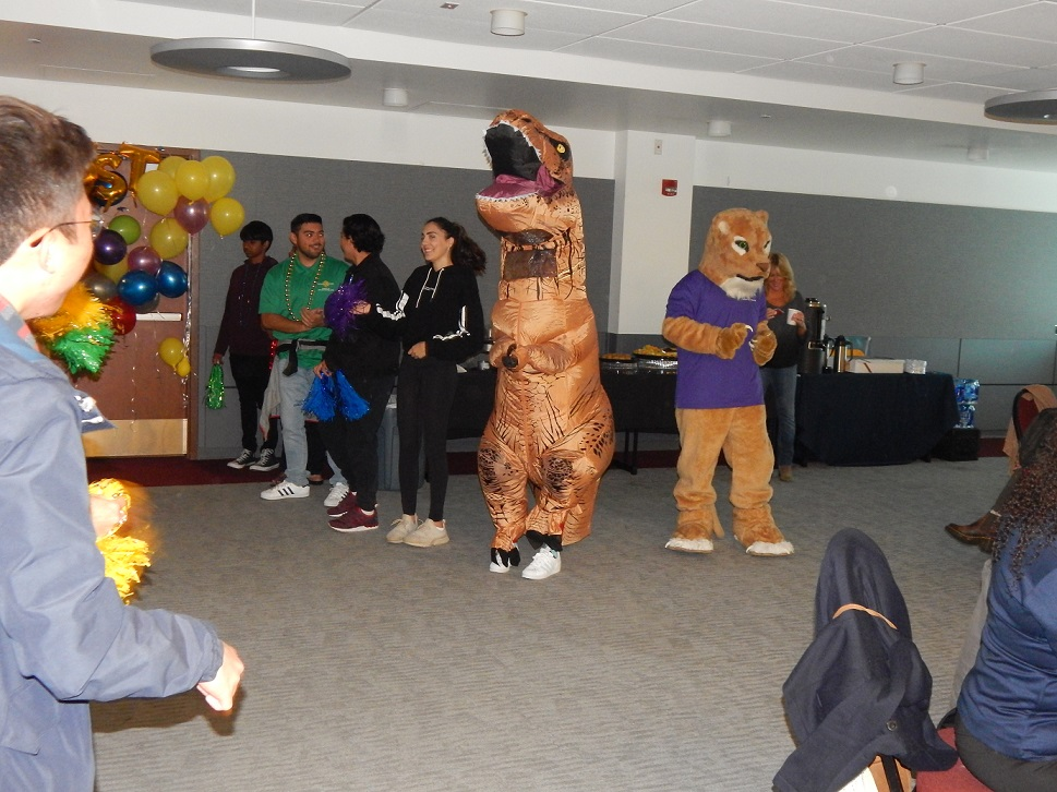 a person in an inflatable dinosaur outfit dancing at the LEAP team party